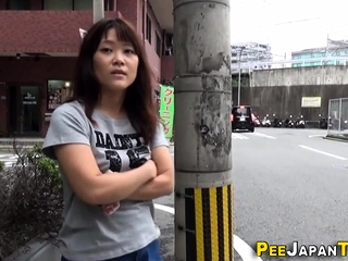 Asian pees a stream onto street